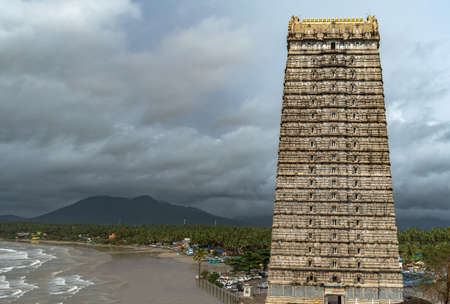 Beautiful view of magnificent 20-storeyed Gopuram tower of Lord Shiva Temple in Murdeshwara with mountains, forest and calm sea waves in background during rainy season. Medieval Dravidian architecture