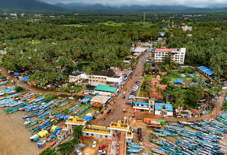 Taken from Drone, a bird's eye view of Murudeshwar city, a coastal town of India with colorful fishing canoes beached at sea shore in off season. Editorial