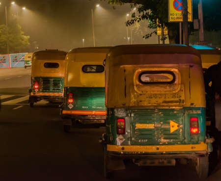 Three wheeled CNG powered Iconic auto rickshaws of India plying on the roads of Delhi downtown during late night commute of foggy Winter nights. - Image.