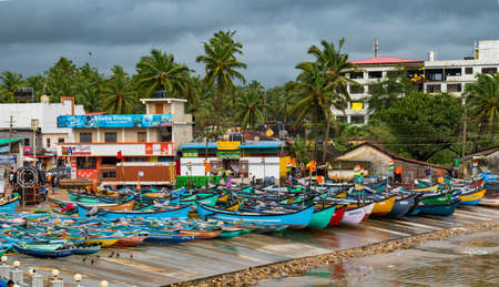 Beautiful photo of coastal beach village on Western ghats of India, where Colorful fishing canoes are anchored off the sea shore during off season and rough weather forecast.