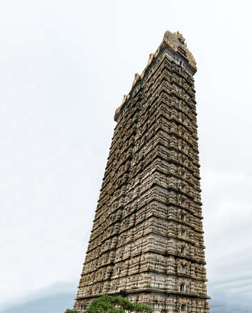 Side view photo of very famous 20-storeyed Gopuram touching the sky at entrance of Lord Shiva temple in Murudeshwar. This grand entrance is made in traditional Dravidian architecture of Medieval India