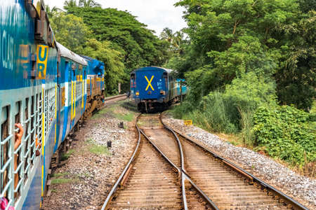 Slow Moving Train of Indian Railways departing from junction and overtaking a halted one amidst greenery of Western Ghats. Editorial