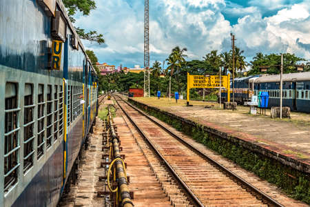 Indian Railways train waiting for green signal to depart at scheduled time from platform of Vasco-Da-Gama station. Amazing sky in background giving photo a poster like look.