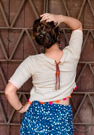 Back View Pose of very Attractive, Young Fashion Blogger, against vintage door in background, wearing ethnic Indian Dress with Crop Top of colorful laces, Patiala Salwar, EarRings, Watch with Hair Bun Imagens - 146684722