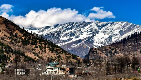 Landscape of snow covered mountains of Himalayas in Background, and in foreground, mountains with deciduous forests with beautiful Hamlet or Village in valley on bright sunny day with cloudy blue sky. Imagens