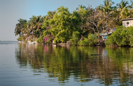 Very Beautiful and scenic view of typical South Indian Coastal Village, wherein an island full of natural vegetation during spring, and its reflection visible in calm water. Sea can be seen at horizon