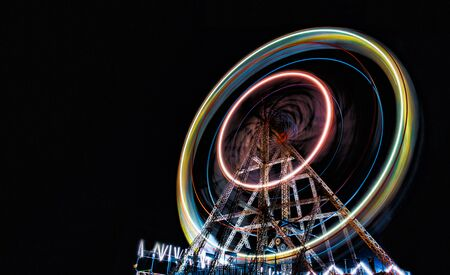 Long Exposure Shot of a well illuminated and colorful Giant Ferris Wheel rotating speedily on its principal axis, during the night hours, in a local fair for the amusement and thrill of visitors.