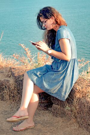 Beautiful and trendy Brunette Indian Girl with curly hair, wearing Blue dress with glasses, watch, slippers, earring, and is  texting from smartphone while sitting on edge of cliff with sea background Imagens