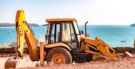 Beautiful Photo of a Yellow Bulldozer machine being used for earth excavation, is parked during lunch time, with serene background of calm blue ocean, with visible horizon - Image. Imagens