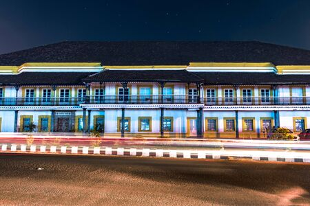 Old Secretariat Building of Goa Government in Panjim, India, during late in night with fast running traffic light trails and stars in sky. Hindi Written Text at entrance means Truth alone Triumphs. Imagens - 147157242