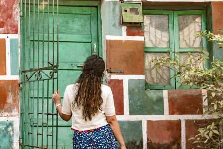 Back view of Teenage girl with golden and curly hairs, posing while opening the gate of her colorful painted house. She is wearing ethnic Indian wear, a white crop top and a blue patiala salwaar.