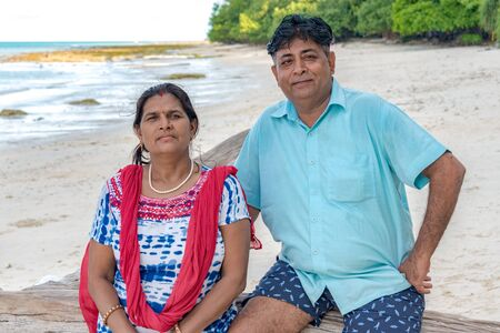 Photo of middle aged, mature and beautiful Indian couple enjoying their vacations at a tropical island. Female wearing ethnic Indian attire and male in casual. They are happy and posing for camera.