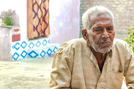 Old Aged Indian male in his 80s, wearing ethic Khadi Kurta, is in deep sorrow and giving a gloomy expression of loneliness and depression. He has wrinkles on face and trimmed white hair. Imagens