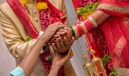 Very beautiful photo of traditional Indian wedding scene of Hindu family wherein priest is blessing the relationship of newly married couple as per vedic culture. Bride and Groom in ethnic dress. Pics Imagens