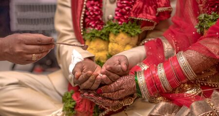 Traditional Indian wedding scene where a beautiful couple is taking part in Hindu rituals of their marriage ceremony. Bride has wore colorful nuptial bangles, while the couple is receiving holy water Imagens