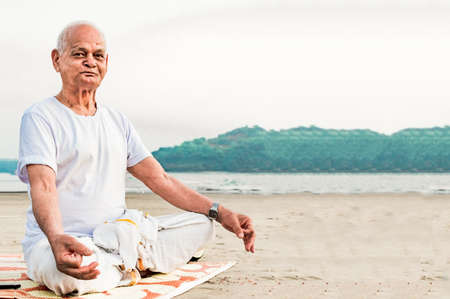 Healthy Old Indian Man, Super Senior Citizen performing Yoga, sitting in Lotus Pose and doing meditation on beach. He is wearing dhoti, has pretty wrinkles on his face and is happily posing for camera Imagens