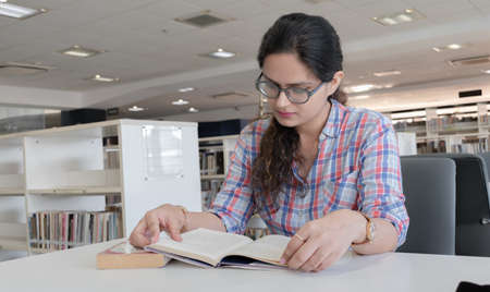 Photo of beautiful and intelligent young girl with eyeglasses studying hard in public library for upcoming exams. Every college going student may connect to this picture for various scenarios. Imagens