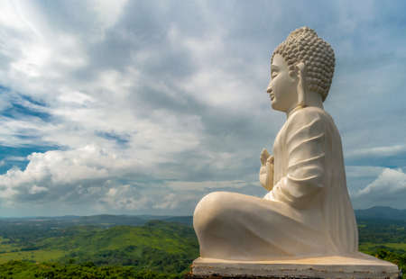 Amazing photo of Lord Buddha statue in white, sitting in meditation pose while giving sermons at top of the hill from where view of entire valley could be seen.