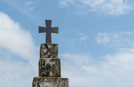 Beautiful photo of holy cross fixed on top of vintage pillar with blue sky and sparse white clouds in background. Visual concept of haunting, exorcism, belief, church, Jesus, cemetery etc - Image.