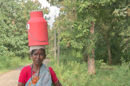 Beautiful photo of an empowered tribal Indian woman in ethnic attire, carrying and balancing milk vessel on her head to deliver it door to door for her customers. Middle aged Hard working woman.