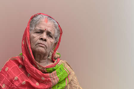 Beautiful portrait of elderly woman from India, having wrinkles on face and white grey hair, wearing colorful ethnic red saree with veil and is thoughtful. Plane background for tagline or advertising.