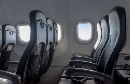 Beautiful cabin interior of passenger airplane, with empty rows of economy class chairs or recliners due to travel restrictions and less demand in tourist transportation due to COVID-19 pandemic. Imagens