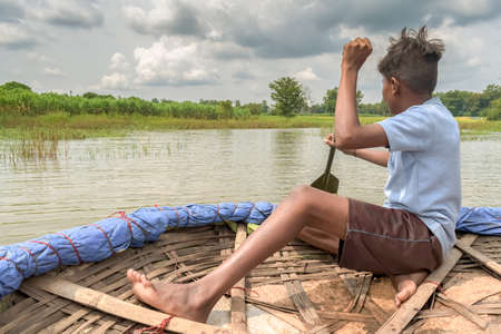 Young teenage boy, a villager rowing a traditional coracle solo, to cross the flooded river for school on outskirts of village. A beautiful Indian scene during summer vacations with rural lifestyle. Imagens