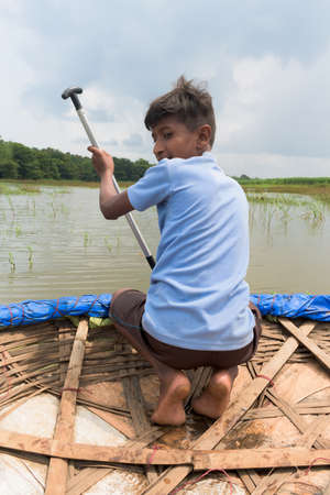 Young teenage boy from rural India rowing a coracle, a traditional bamboo made, while fishing in the flooded river or lake after his school hours for some adventure. He is boating and paddling solo.