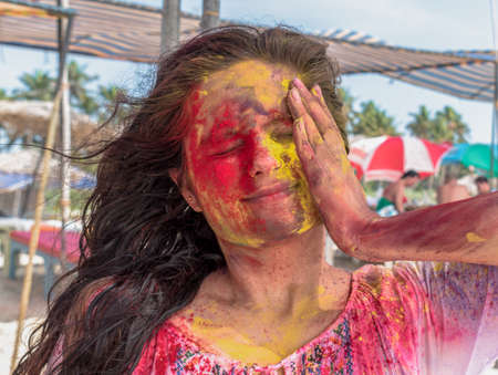 Amazing candid photo of young girl playing and enjoying Holi, festival of colors in India. Applying vibrant shade of colors on her face by hand and closed eyes as she is taken by surprise. - Colorful Imagens