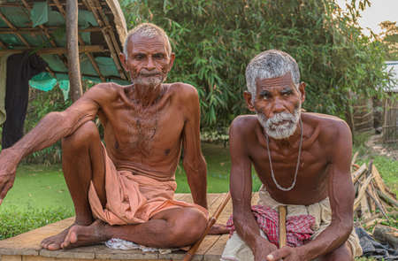 Beautiful image of two tribal Indian farmers or daily wage laborers, old aged yet healthy males sitting together for rest after hardwork and posing for camera while in deep thoughts about their future Imagens