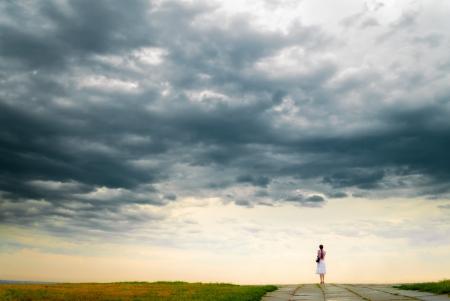 Meisje kijkt naar bewolkte hemel van bluf