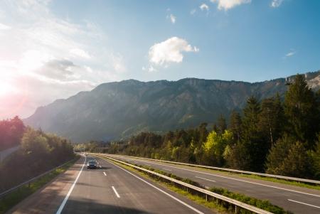 Autobahn in de Oostenrijkse bergen bij zonsondergang Stockfoto