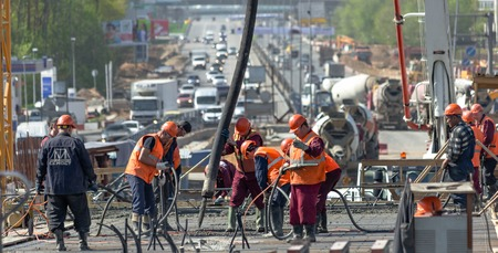 superstructure: MOSCOW - MAY 2  Road workers concrete the superstructure opposite heavy traffic on May 2, 2014 in Moscow