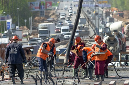 superstructure: MOSCOW - MAY 2  Road workers concrete the superstructure opposite heavy traffic on Novoryazanskoe highway on May 2, 2014 in Moscow  Novoryazanskoe highway is a part of the Ural Highway wich is a road from Moscow to the Ural Mountains