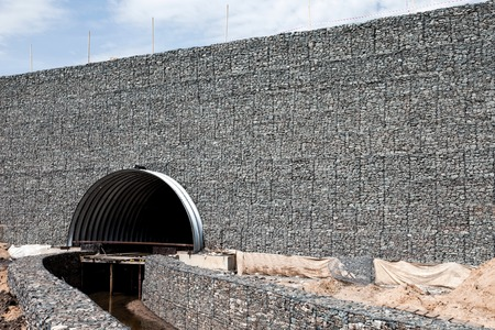 gabion mesh: Erosion protection by gabions with tube under the road Stock Photo