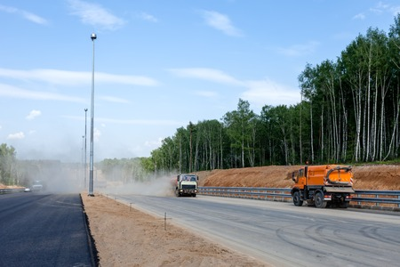 hiway: Street sweepers with clouds of dust at the road construction