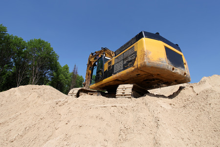 Excavator on a hill of sand photo