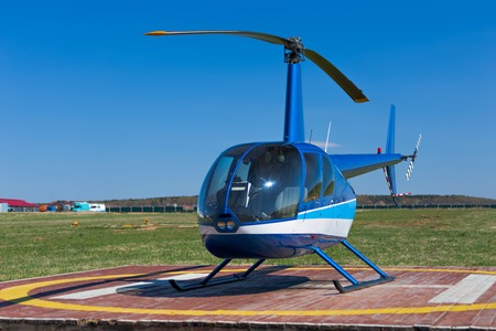 landed: Front view of small blue landed helicopter