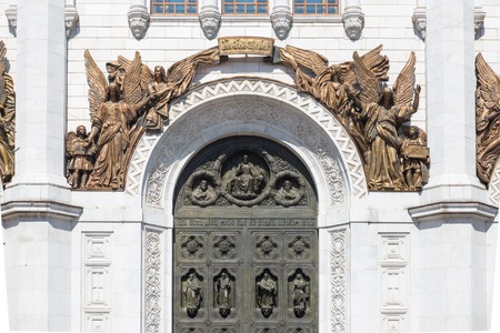 charter: Arch above the large middle gate of the Cathedral of Christ the Savior in Moscow, Russia. The high relief with  four angels with outspread wings, holding the charter that says - Gods Power with us and two angels.  The image of the blessing Christ the S Stock Photo