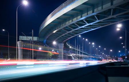 iluminado: Paso superior y estelas de luz en la noche en la carretera iluminada