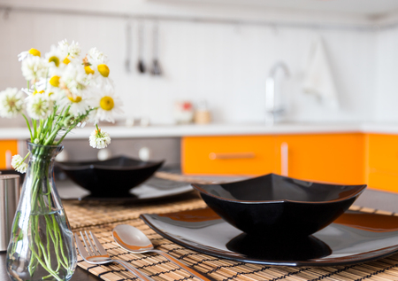 camomiles: Table served in the kitchen with black dishes and camomiles
