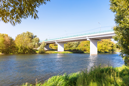 Concrete bridge across the river with grass on the foreground