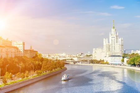 kotelnicheskaya embankment: Kotelnicheskaya embankment with leisure boat floating across the Moscow river on a sunny day Stock Photo