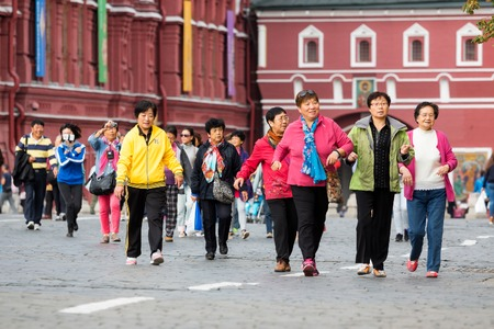 sightseeng: MOSCOW - SEPTEMBER 22, 2015: Group of chinese tourists walking on the Red Square. This place is considered as the most popular sightseeng in Russia. Editorial
