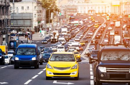 Zwaar verkeer op de stadsweg met gele taxiauto op de voorgrond Stockfoto