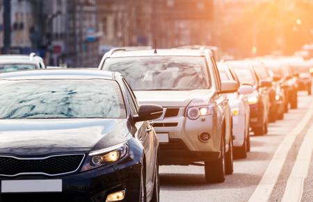 Close-up van de baan van auto's in verkeersopstoring tegen de zon