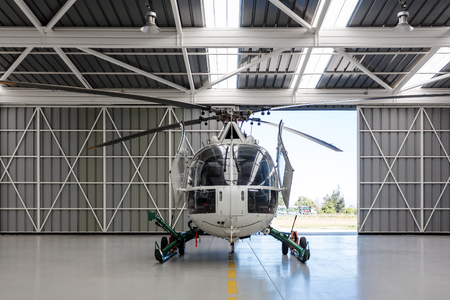 Rear view of the white clean helicopter situated in the hangar