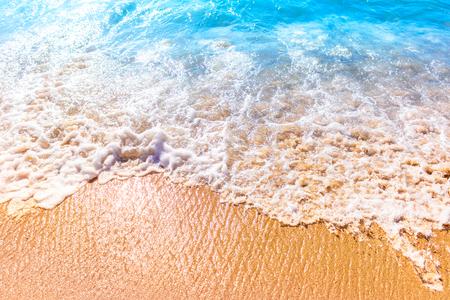 Overzees schuim op het zand op zonnige dag Stockfoto