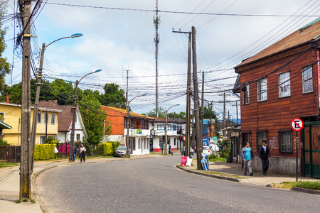 VALDIVIA, CHILE - OCTOBER 29, 2016: People walking on the sidewalk of the empty road of Anibal Pinto street.