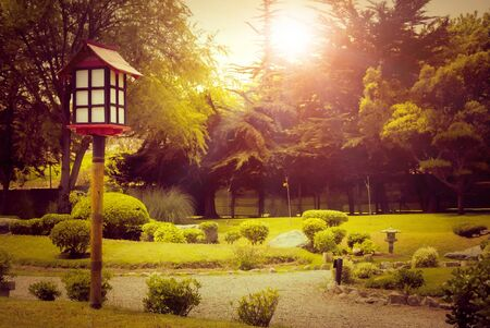 Closeup wtih decorative wooden lantern in japanese garden at sunset in La Serena, Chile Фото со стока